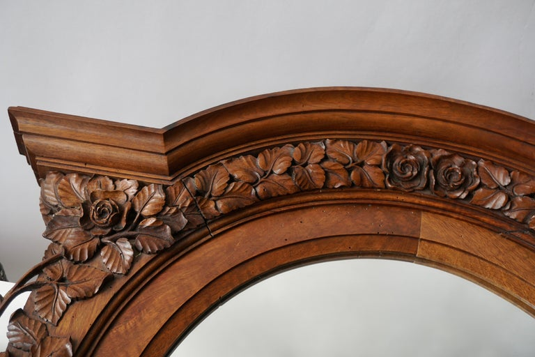 An impressive Italian carved wood wall plaque with center mirror from the early 20th century. This antique wall decoration from Italy features ornate three dimensional hand carvings in a shell, floral, and scrolling leaf motif, about a framed mirror