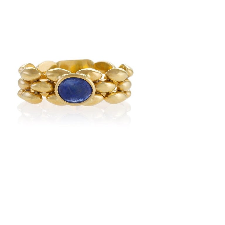 A modern Italian 18 karat gold flexible chain link ring with sapphire. The entirely flexible band of the ring features a fetching woven pattern in high polish. The ring centers on a cabochon sapphire with an approximate weight of .90 carat. Circa