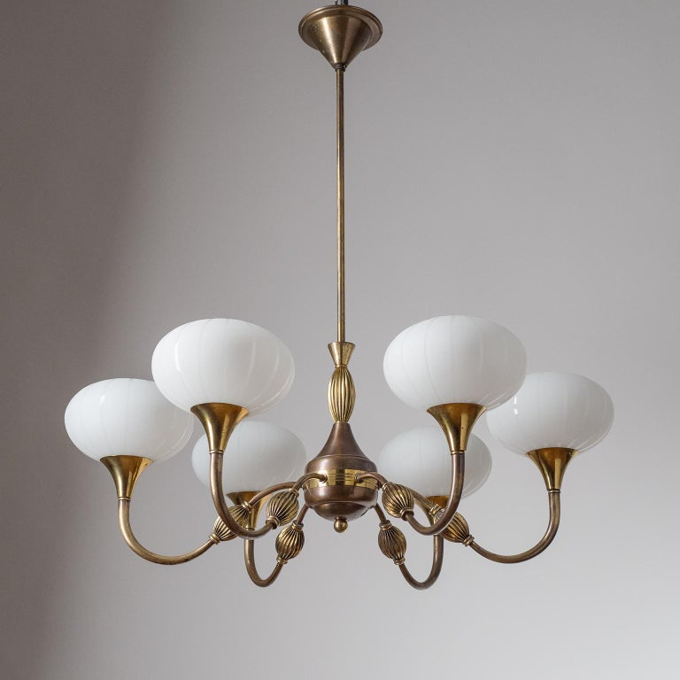 Italian six-arm brass chandelier from the 1940s. Rare 'pleated' brass decorations on arms and body and blown milk glass diffusers with satin-etched stripes. Original brass and ceramic E14 sockets with new wiring. Height without the stem is