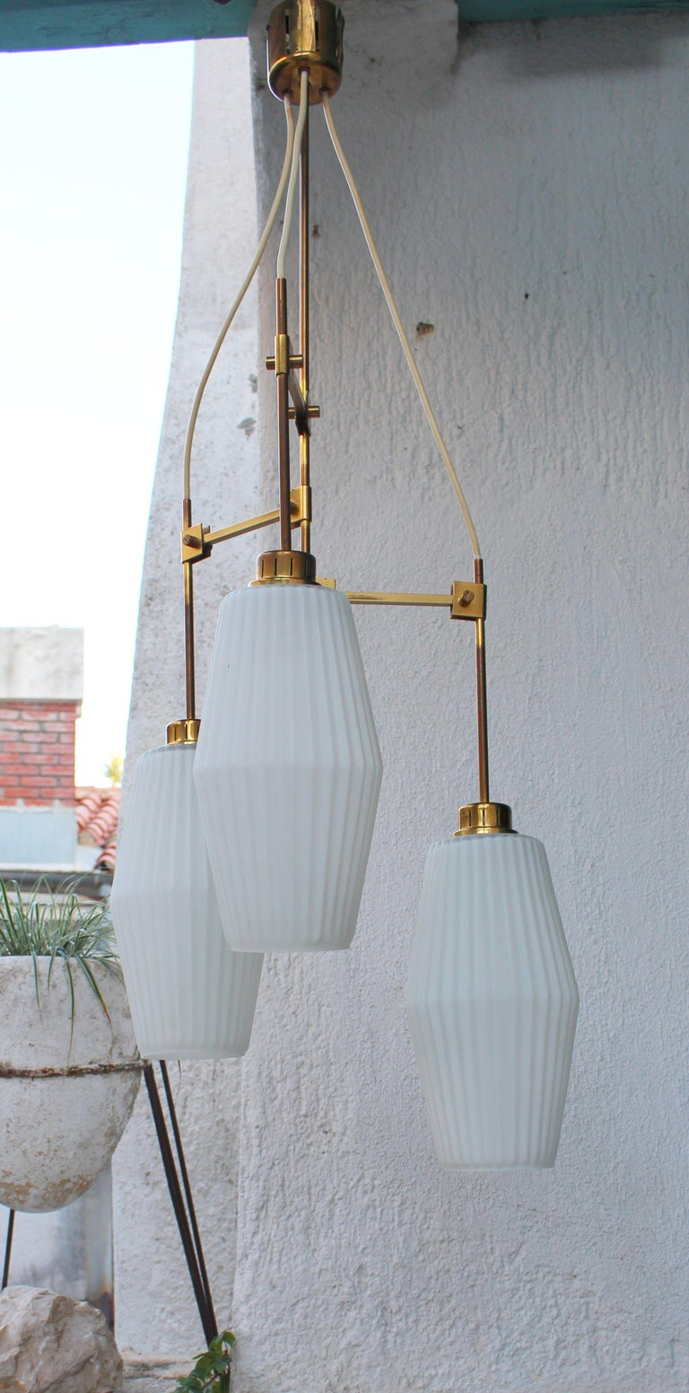 Italian brass chandelier, 1940s. Brass and white ribbed glass, one of the glass shade has a little chip circa 1/16 of the inch. We can covered with the emulsion and will not be notice.