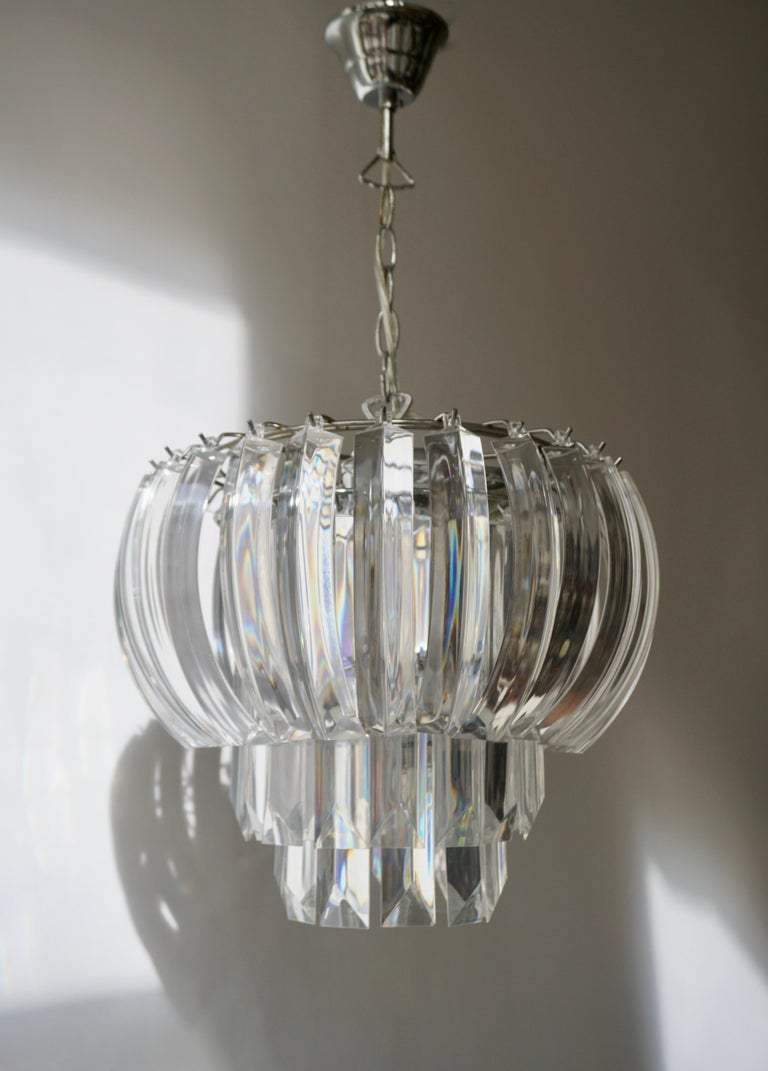 A waterfall chandelier comprised of prismatic plastic sections with angled ends.  Measures: Diameter 38 cm. Height fixture 30 cm. Total height including the chain and canopy 80 cm. The light requires three single E14 screw fit light bulbs