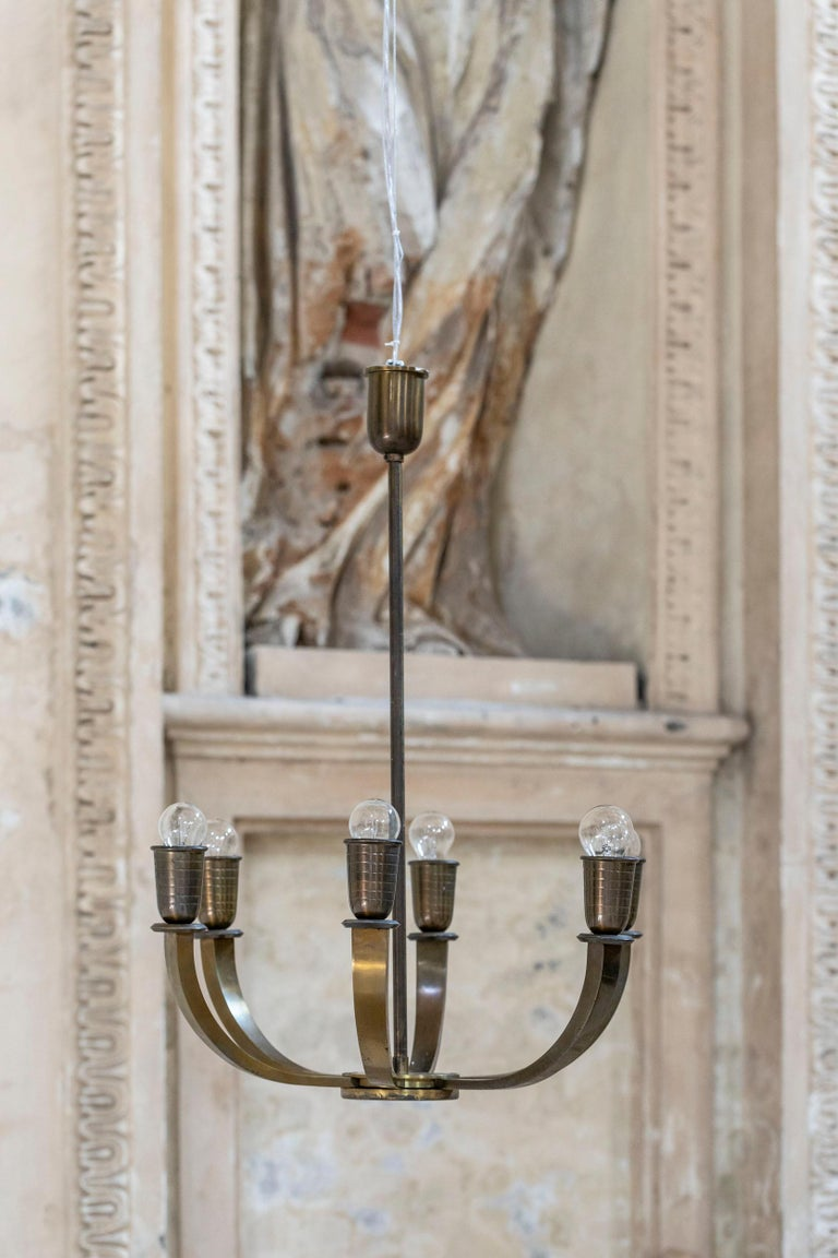 Stunning chandelier in solid brass. Six thick chiseled arms, with engraved brass light bulbs. Excellent conditions.