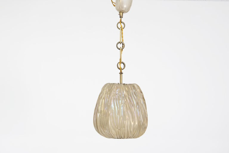 Magnificent Venini pendant in irridescent glass from the 1940s. The pendant is made of 9 segments in irradiated glass, inside each segment there are beautiful grooves where the light of the glass reflects to create beautiful play of light. Each