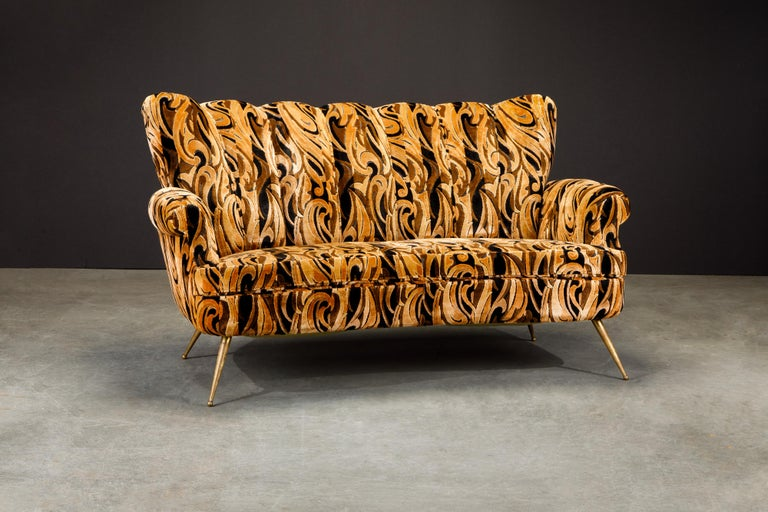 This gorgeous Italian Mid-Century Modern loveseat features a channel tufted fluted cushioned back over a curve shaped seat in brown and black cut velvet upholstery rising on tapered brass legs. Such groovy fabric, get this for your interior design