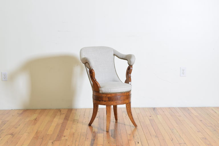 This unusual chair has a sloping back with high, upholstered arms and is a slightly later rendition of an Empire period chair, constructed of maple and rosewood veneers, raised on splayed legs the arms are atop almost swan-like shaped supports,