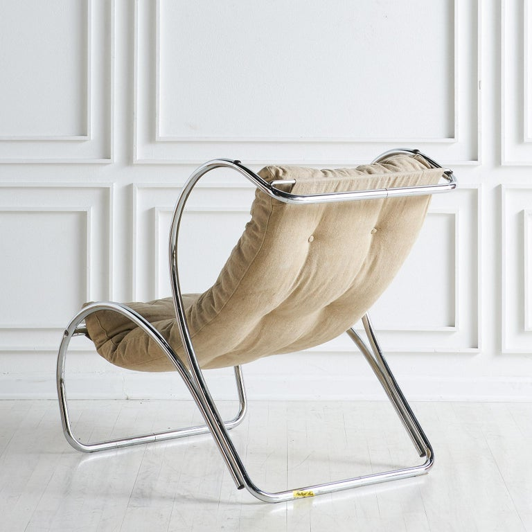 Cushioned chair in a flaxseed colored linen fabric and with chrome accents. Sourced in Italy.