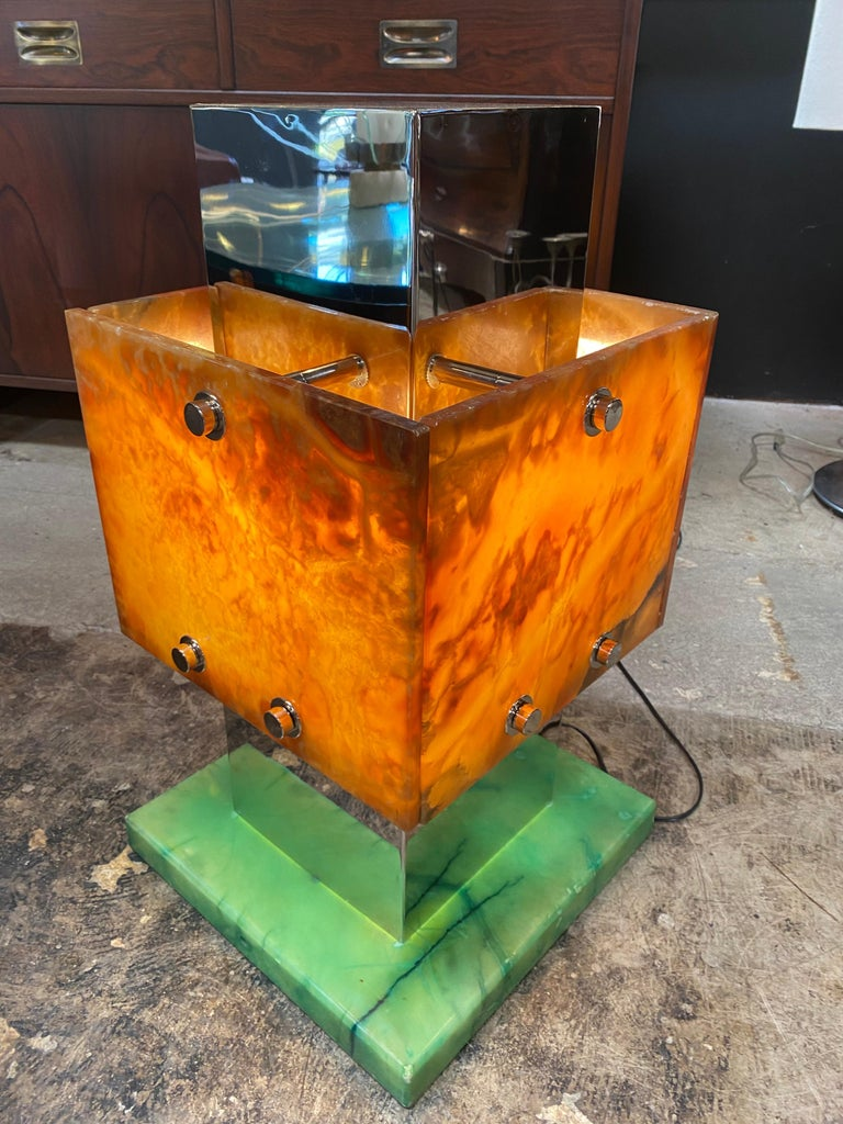 The body of this geometrical lamp is composed of two solids, one chrome and one (the shade) with an amber Lucite finish cut by hand. The square Lucite base is 13 x 13.