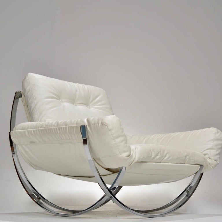 This lounge chair and ottoman by Stendig is quite the show stopper.  It features overlapping curvilinear supports in chrome that attach to the base of each piece. It may look like a rocking chair but it is actually stationary.  The ottoman and