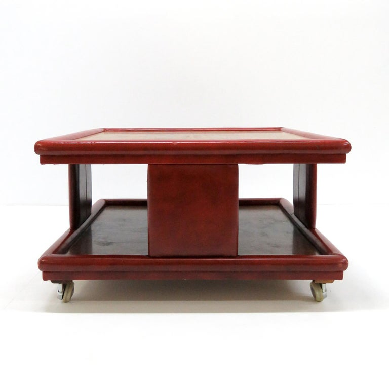 Wonderful red leather and wood two-tier coffee table from Italy, 1970, attributed to Poltrona Frau. One dark one light wood top, great patinaed leather cladding on detachable casters.