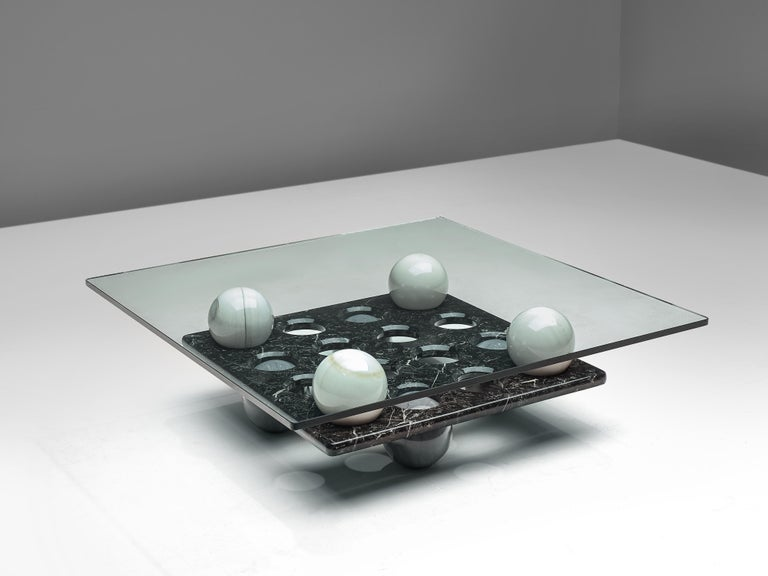 Cocktail table, glass, marble, Italy, 1970s  This coffee table consists of two layers, divided by eight marble spheres in white and dark grey color. The top is made of glass, while the second layer is made of black marble with circular gaps. The 16