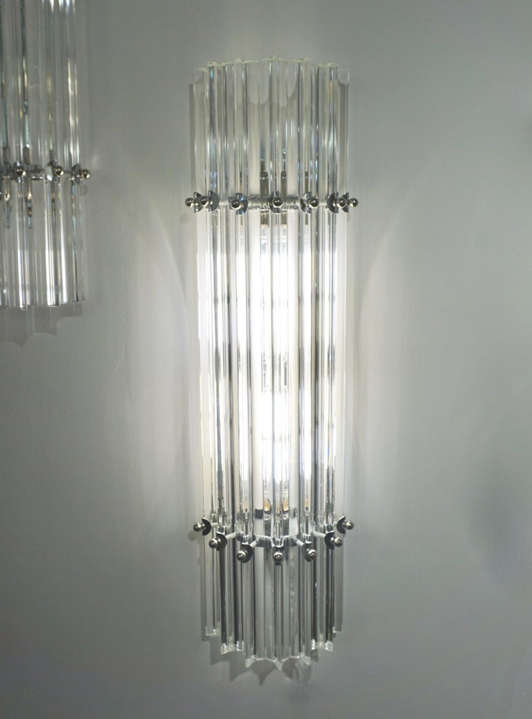 Very sleek custom Venetian pair of wall lights with organic minimalist design, consisting of seven straight crystal clear Murano glass rods of triangular section with amazing concave sides, that not only highlight the curved design but amplify the