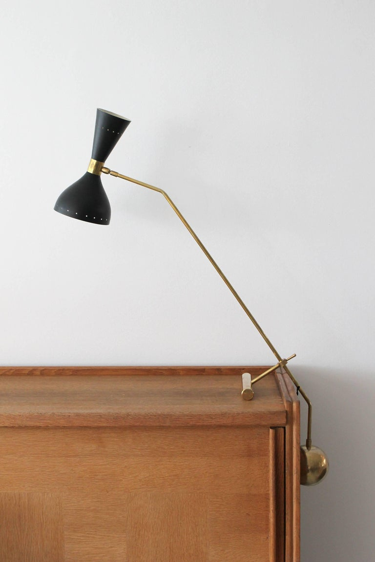 Italian desk lamp with heavy brass counterbalance weight, black cone shade that lights up and down.