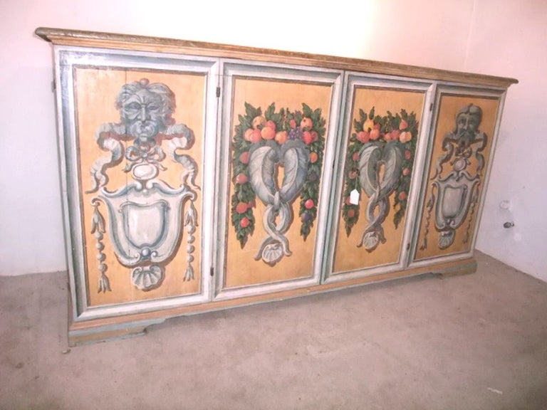 Magnificent Italian credenza with painted doors, could be a master piece for a large entrance or a living room in a mediterranean style mansion .The hard ware are wrought iron. Each painting on each door is an excellent piece of art in the Italian