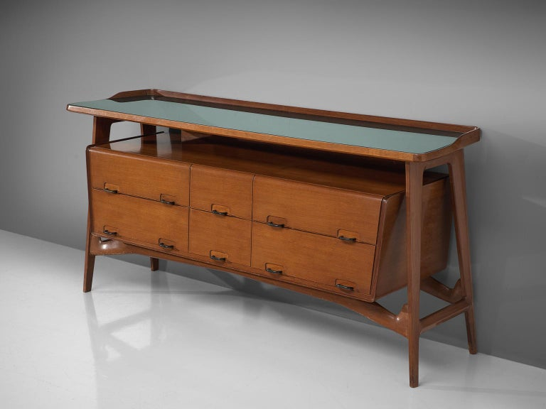 Credenza, fruitwood, glass, brass, Italy, 1950s  This sideboard is both refined and elegant in every way. The glass top stretches slightly over the outer edges of the solid, precisely crafted legs. This piece is playful and airy. The biomorphic