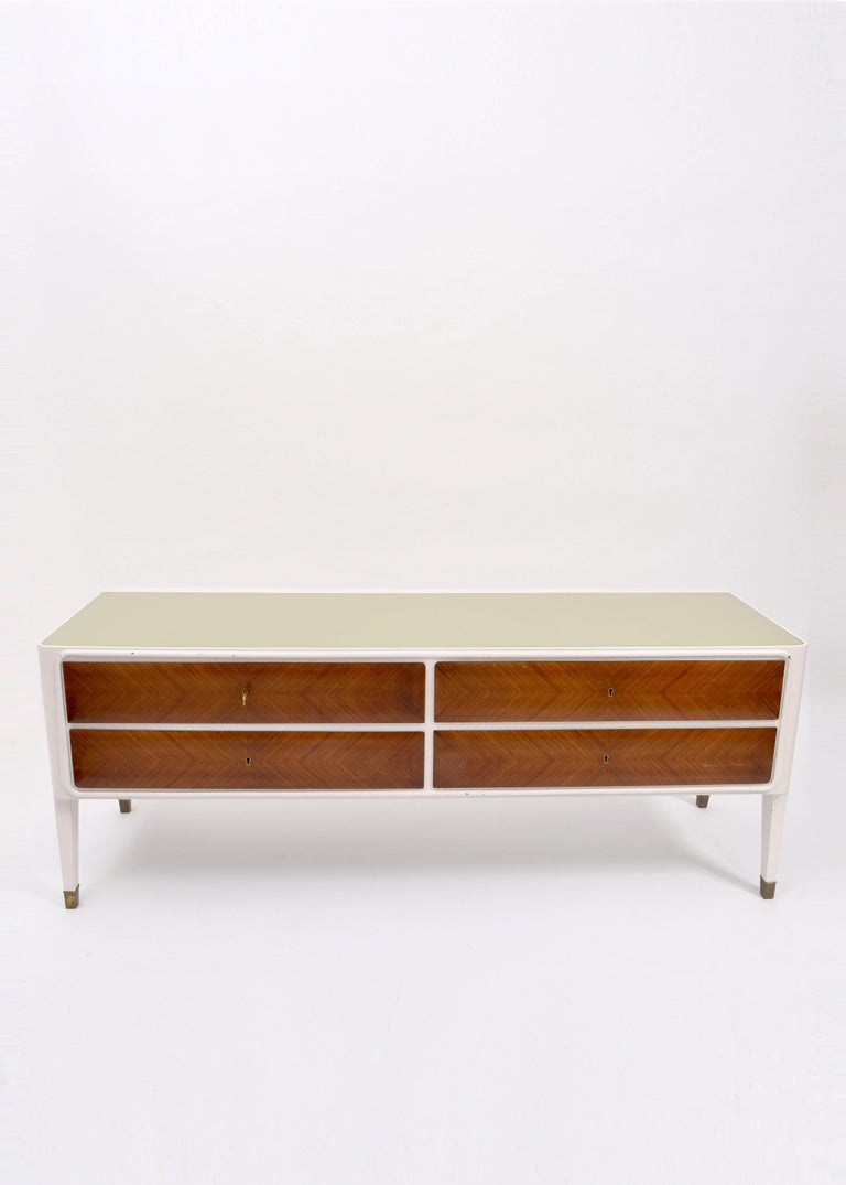 Italian credenza sideboard, circa 1950. White lacquered cabinet with wooden drawers and set-in opaque glass top. Brass feet details, escutcheons and key.
