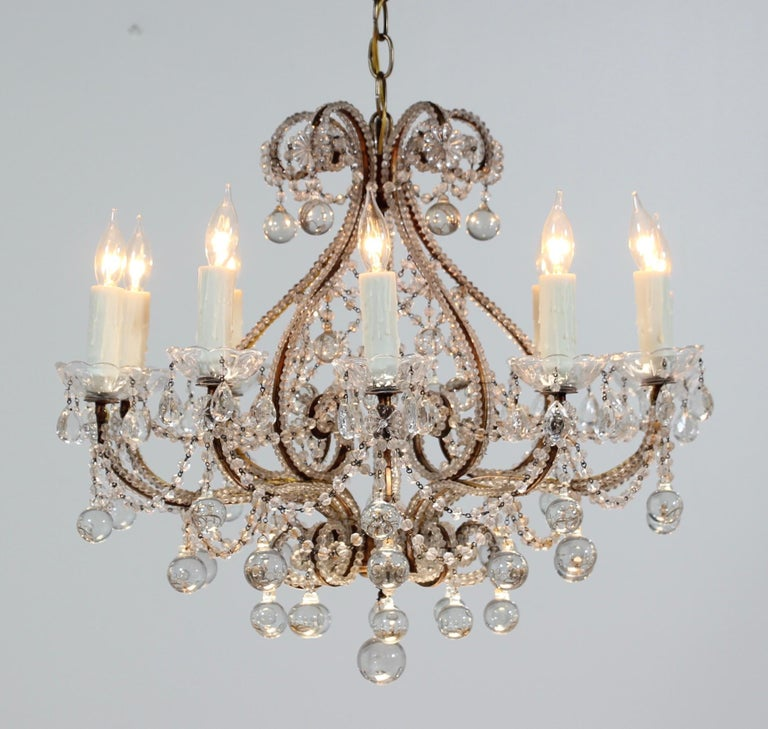 """Beautiful, 1940s Italian gilt iron and crystal beaded chandelier. The chandelier consists of a curvaceous gilded iron frame which has been hand beaded with """"English cut"""" beads. Glass ball drops in a variety of sizes complete the chandelier's"""