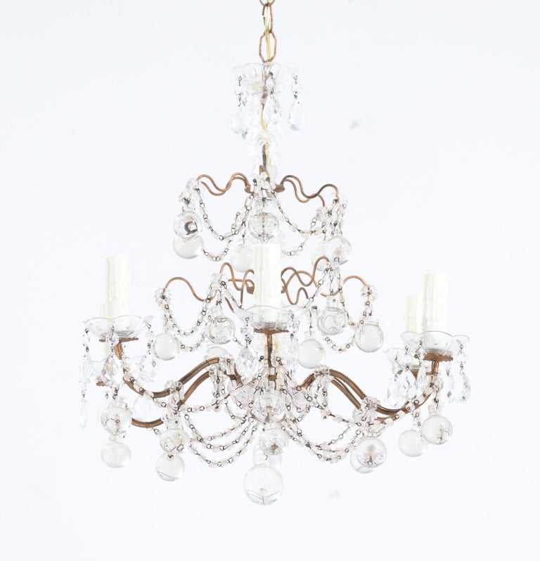 Graceful, 1950s Italian gilt-iron and crystal beaded chandelier.  The chandelier consists of a scrolled gilt-iron frame with a glass column at its center. The chandelier is beautifully decorated with macaroni bead swags and large glass ball