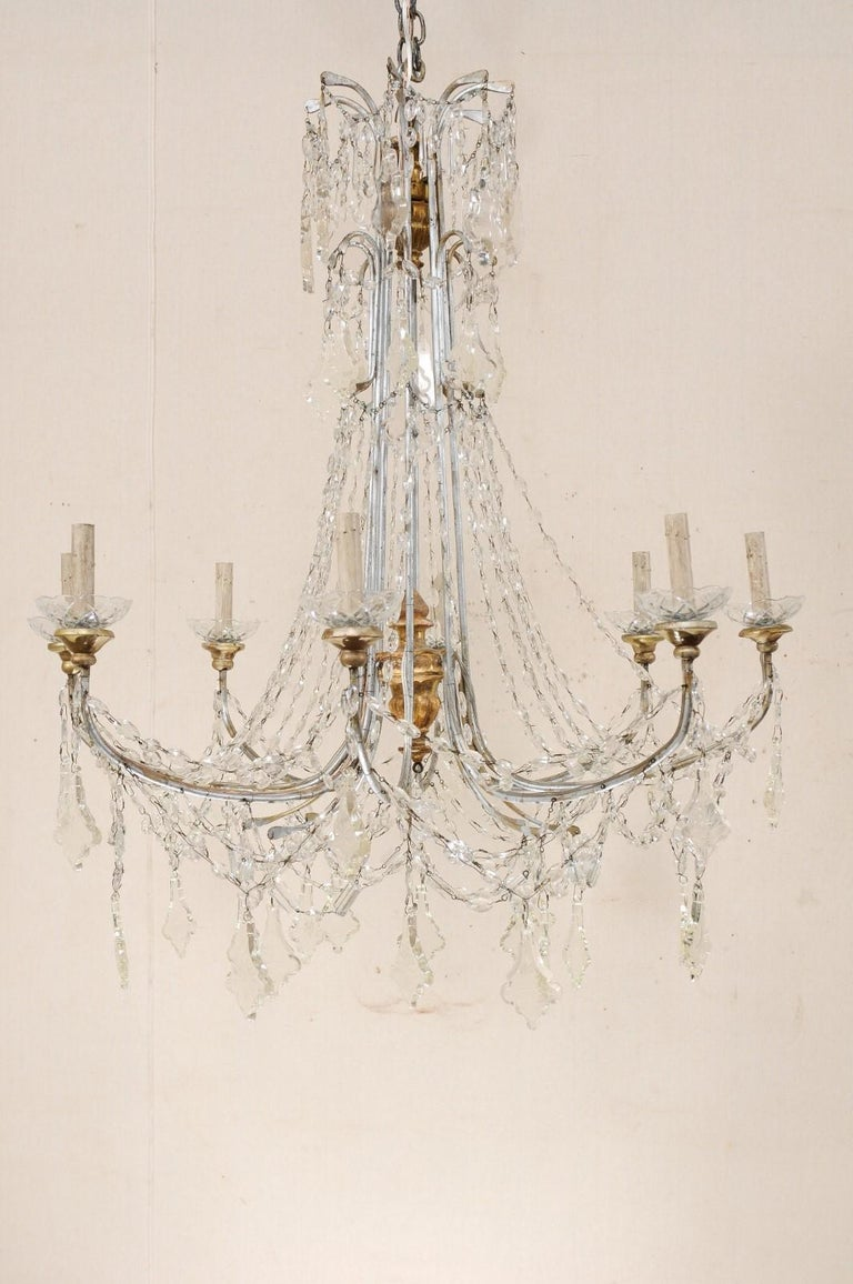 An Italian crystal eight-light chandelier from the mid-20th century. This vintage chandelier from Italy features swooping strands of Italian glass which flow downward from the two-tiered crystal waterfall top. The eight silver metal arms are draped
