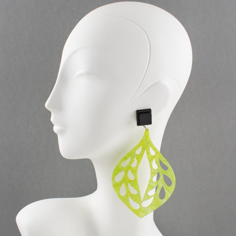 Spectacular Italian designer studio Lucite or resin dangling shoulder-duster clip-on earrings. Oversized drop shape all carved and see-thru in lime green color with a moon-glow textured pattern. Clip fittings in black color with a laminated pattern.
