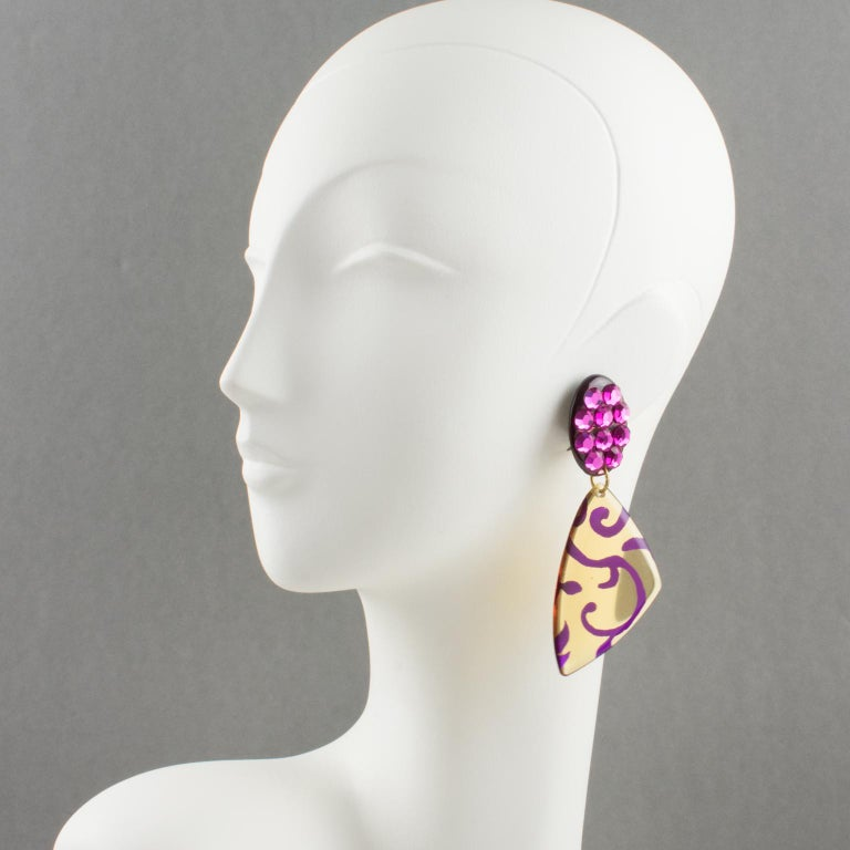 Handsome Italian designer studio Lucite dangling clip-on earrings. Chandelier shape with geometric carved design in luminous transparent apple juice color with floral fuchsia purple design. Clip fittings all paved with hot pink crystal rhinestones.