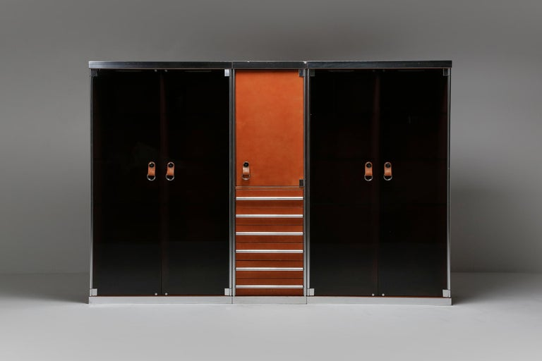 Guido Faleschini showcase, dresser, designed for the Hermès shop in Paris, Mariani Italy 1970s  consisting of one Hermès cognac leather drawer chest with shelves, flanked by two showcases with glass shelving and lights, finished with chromed steel