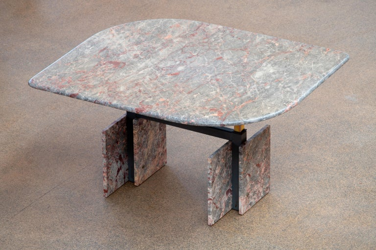 Beautiful grey, beige and pink marble table.  The heavy eye-shaped heightenable top rests on four marble blocks with a metal structure between.