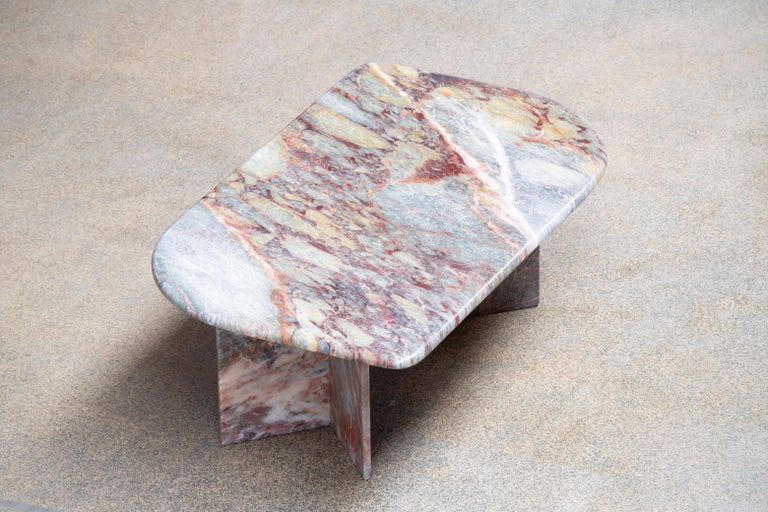 Beautiful grey, white and red marble table.  The heavy eye-shaped top rests on two marble V blocks.