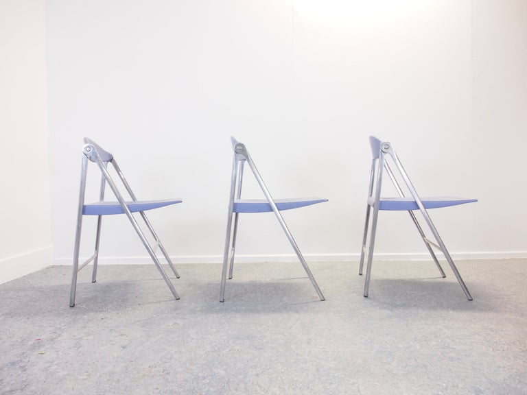 Very rare and exclusive set of 3 vintage folding chairs by Poltrona Frau with lavender/pastel blue leather upholstery.  The chairs are made of a cast aluminium ingenious folding construction with a lavender/pastel bleu leather upholstery and