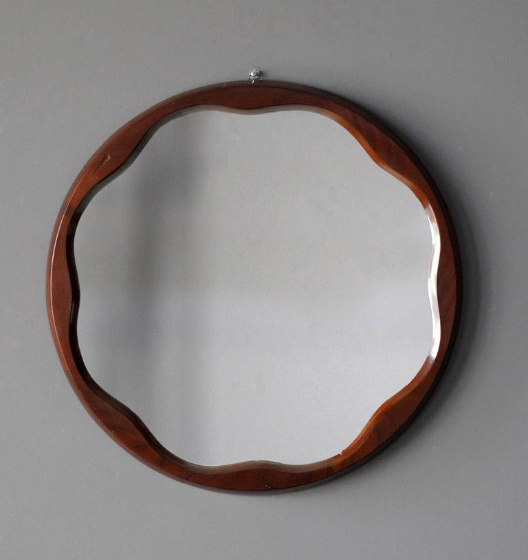 An organic wall mirror, produced in Italy, 1950s. Cut mirror glass is framed in finely sculpted walnut frame.  Other designers of the period include Gio Ponti, Fontana Arte, Paolo Buffa, Franco Albini, and Jean Royere.