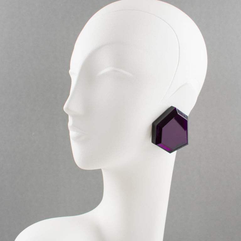 Beautiful oversized Lucite clip-on earrings from artisan designer studio. Huge flat geometric shape with intense purple color (fuchsia overtone color when placed in strong light) and large beveling.  No visible maker's mark. Measurements: 2.07 in.