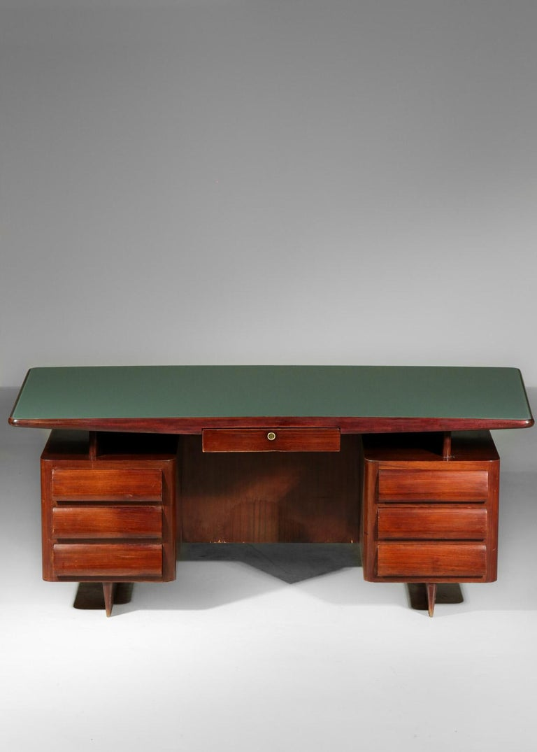 Desk designed by Vittorio Dassi and composed of a floating top with a green glass supported by 2 drawers on each side, made in walnut.