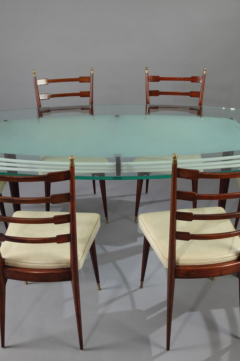 White lacquered metal table with glass top resting on four slender oak feet. 1960s Italian design. Six chairs in mahogany and leather imitation decorated with brass finials, 