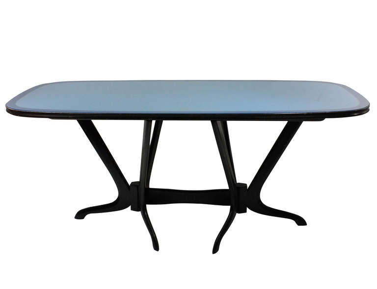 An Italian dining table with an unusual sculptural base. The base is a dark rosewood color and is hand carved which supports a top consisting of an inset blue glass top with a border and gold etched design.