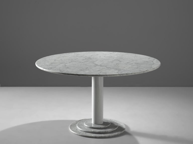 Round dining table, white marble, Italy, 1970s  This table is a skillful example of Postmodern design. A white lacquered metal pedestal with a marble foot holds a round marble table top. A great classic designed in the style of Acerbis. The foot