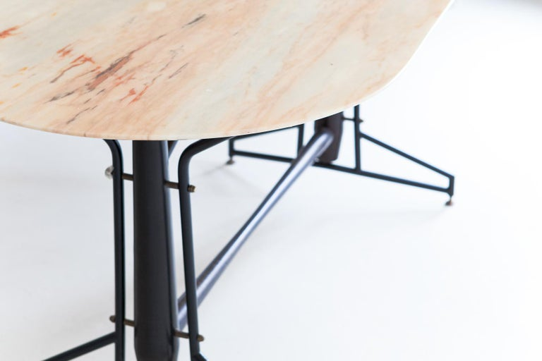 A dining table, manufactured in Italy during the 1950s   This interestingly designed table has a frame made of iron and wood with brass details. A large marble top is placed on it. The base of the table has been restored. The marble top has some