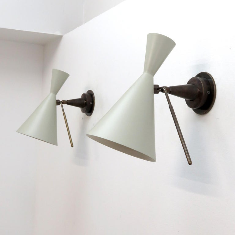 wonderful articulate Italian wall lights with off-white/light grey enameled double cone shades on dark patinaed brass armature with a pronounced handle for shade adjustment, wired for US standards, one E27 socket per fixture, max. wattage 100w each,