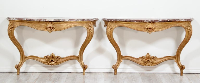 Fantastic, pair of early 20th century Italian Louis XV style carved gilt-wood console tables with marble tops.   These antique consoles feature beautifully carved gilt details including curvaceous cabriole legs, rocaille stretchers and cartouche