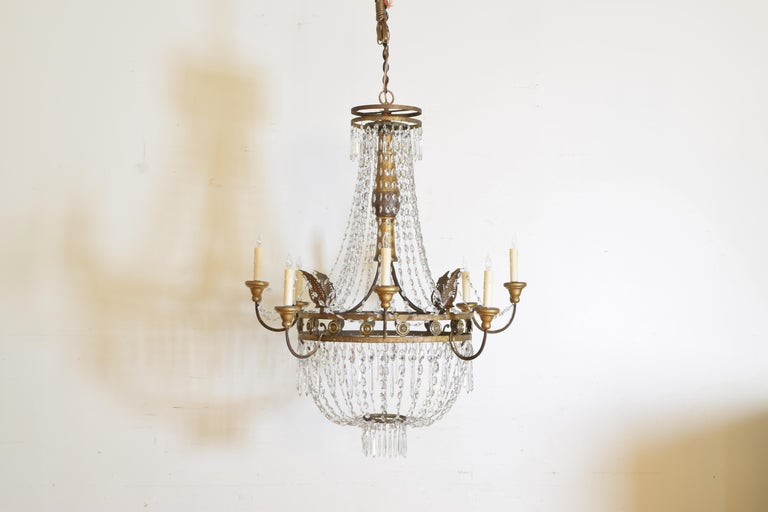 Hanging from its original loop, the top having two gilt metal rings, having a turned and carved giltwood standard, the outer gilt metal ring with brass concentric discs, the frame issuing eight arms of alternating heights, all with giltwood