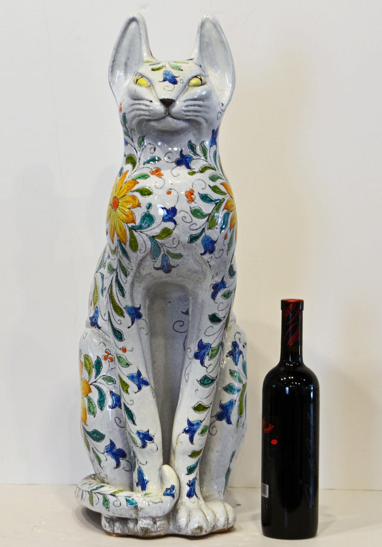 Standing 27 inches tall this Italian Egyptian inspired terracotta statue of a beautifully glazed and decorated cat is a feast for the eyes. It dates to the late 20th century and is a fine representative of the centuries old Italian majolica