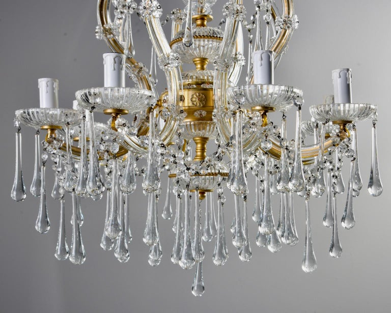 Italian crystal chandelier features eight arms with candle style lights and candelabra sized sockets, etched bobeches, gilded metal frame embellished with etched glass spacers, crystal beading and flowers, circa 1920s. Bobeches and arms are hung