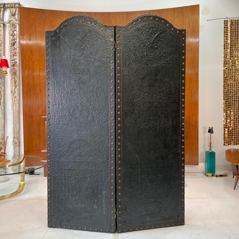 Two panel Italian floor screen (paravent / divisore) room divider in embossed Florentine leather on a hinged wood frame backed with blackened cotton duck canvas embellished with decorative bronzed metal tacks, circa 1928. Overall distressed