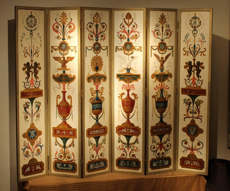 This one-of-a-kind museum quality early 19th Century room divider folding screen is made up of 6 rectangular wood panels, each richly painted and lacquered with architectural motifs, vases,  musical allegories,flowers details, putti, grotesque and
