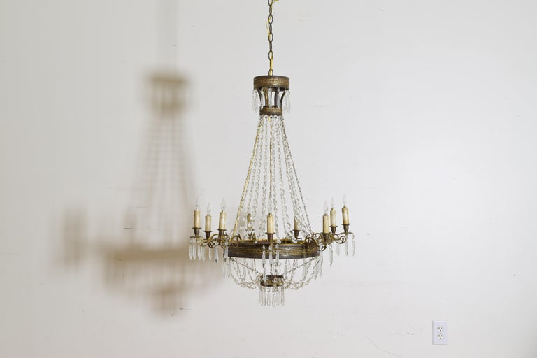 The chandelier of typical basket form with four round sections connected by graduated bead chains, the largest and central ring issuing 9 cast brass arms with bobeches and hanging prisms, the upper and lower rings also with hanging prisms, 19th