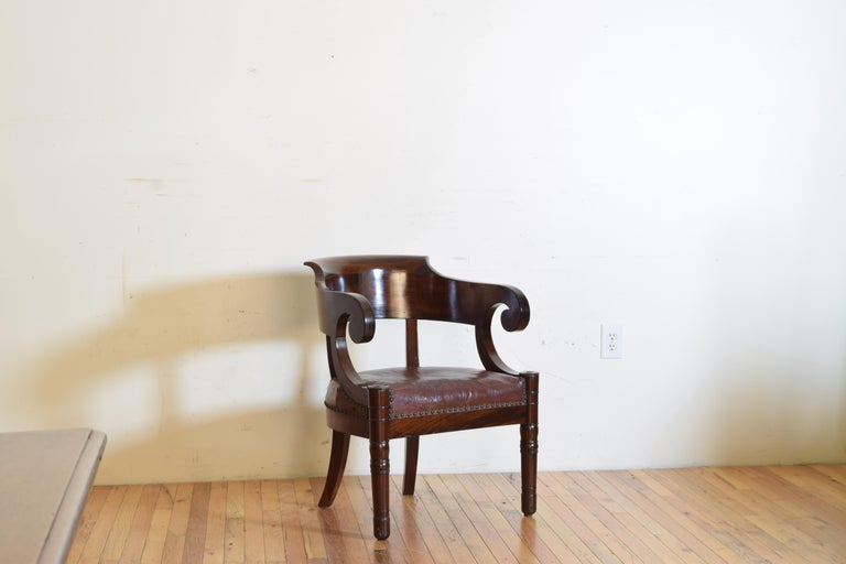 Having an open concave back with shaped undercurled handles, the maroon leather upholstered fitted seat resting on turned and tapering front legs and splayed rear legs, first quarter of the 19th century.