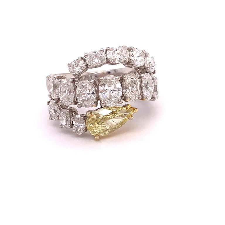 This one of a kind high fashion diamond ring features a 1.79 carat pear shape fancy yellow diamond with SI2 clarity. There are seventeen beautiful oval cut diamonds weighing 3.53 cttw.  They are F color and VVS Clarity.  This is set in 18Kt white