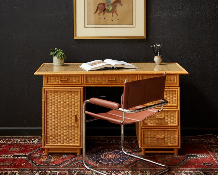 Mid-Century Modern Italian pedestal style writing table or desk. Crafted in the Campaign style with a removable top section and two pedestals. The case features decorative carved faux bamboo trim and wicker rattan inset. The top of the desk has a