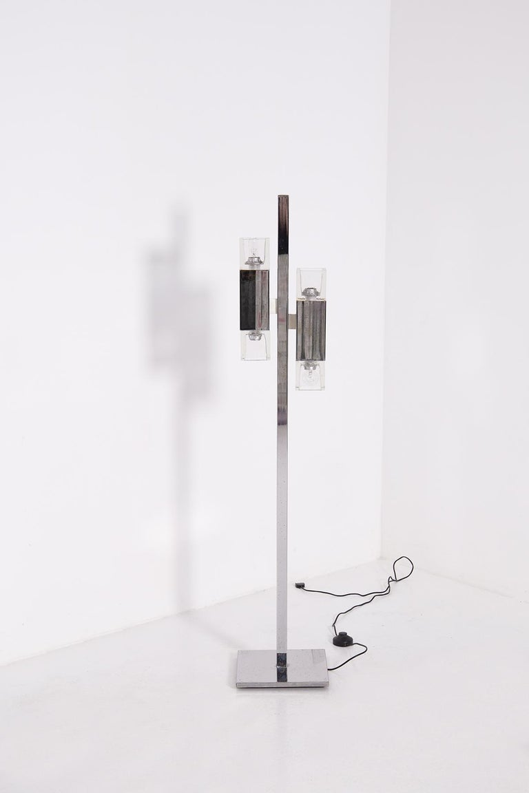 Italian floor lamp from the 1970s.  The floor lamp is made of chrome-plated steel. It is supported by a square pedestal also made of chrome-plated steel and a stem that holds two lamp holders. At the ends of the lamp holder we find the two thick
