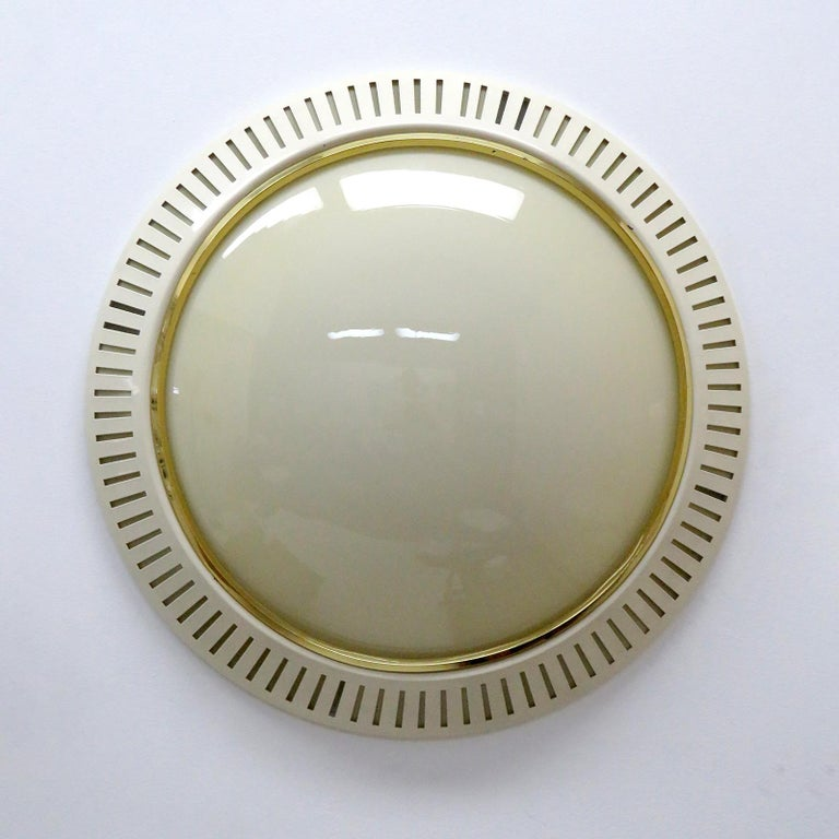 Wonderful large-scale flush mount with an beige colored glass diffuser held by a perforated eggshell colored metal enclosure with brass ring, can be used as wall or ceiling light.