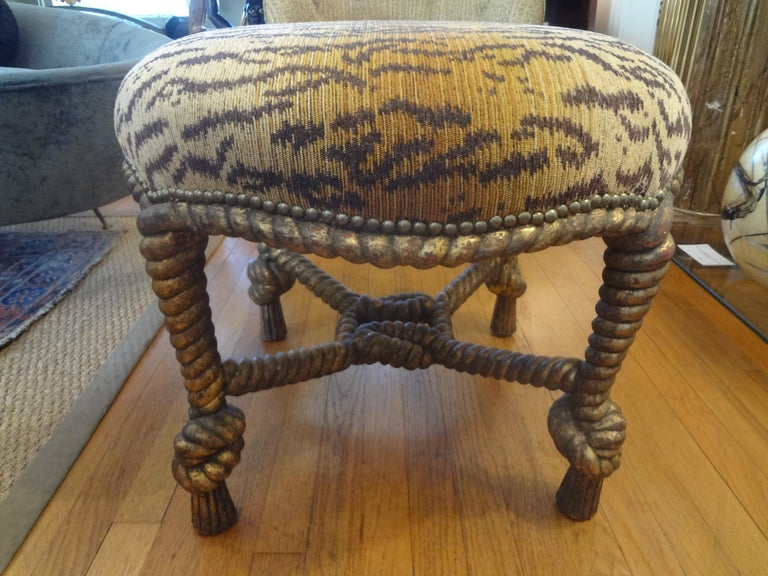 Stunning Italian A.M.E. Fournier style, Louis XVI style, or Napoleon III style carved giltwood knotted rope and tassel ottoman. This large and comfortable ottoman, stool, bench or tabouret is currently upholstered in leopard chenille fabric with