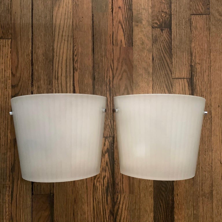 Pair of Italian, fluorescent wall sconce lights by Rodolfo Dordoni for Artemide feature curved, ribbed, frosted glass shades with chrome hardware on metal backplates. The sconces taper in height from 9 - 11 inches.